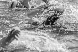 person swimming across the channel black and white image